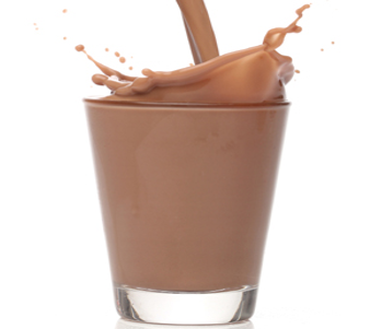 chocolate milk being poured into glass