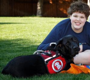 boy sitting on grass with black service dog next to him