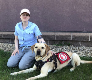 woman kneeling outside with hand on yellow Lab service dog lying next to her