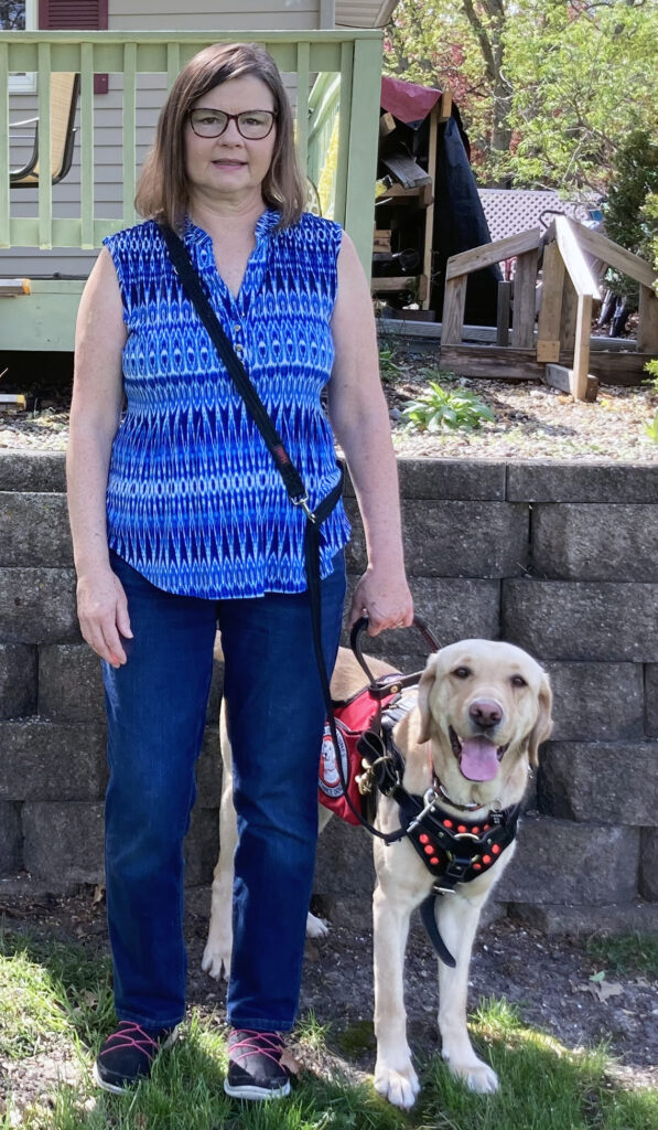 woman in blue blouse standing in front yard holding harness of service dog standing next to her