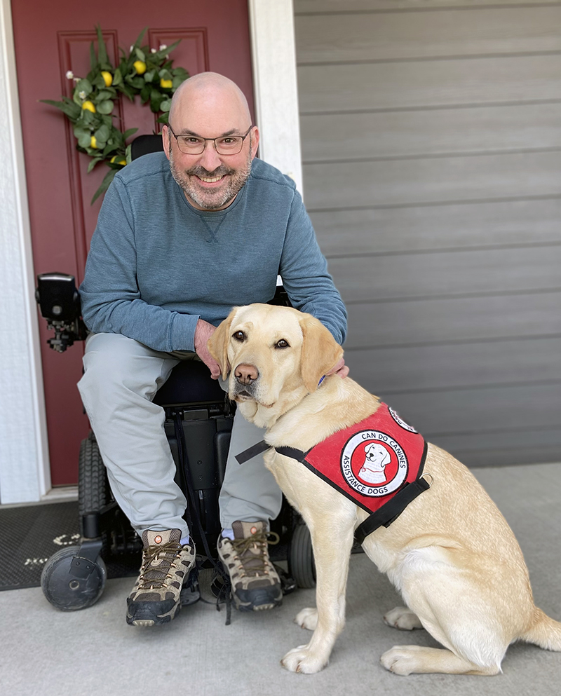 man sitting in wheelchair outside home with service dog sitting in front of him