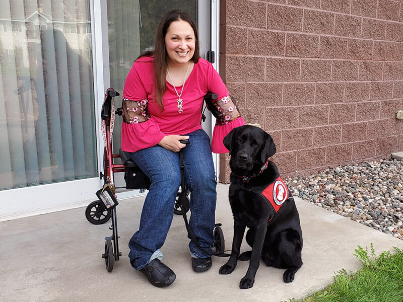 woman sitting on outdoor patio in wheelchair next to service dog