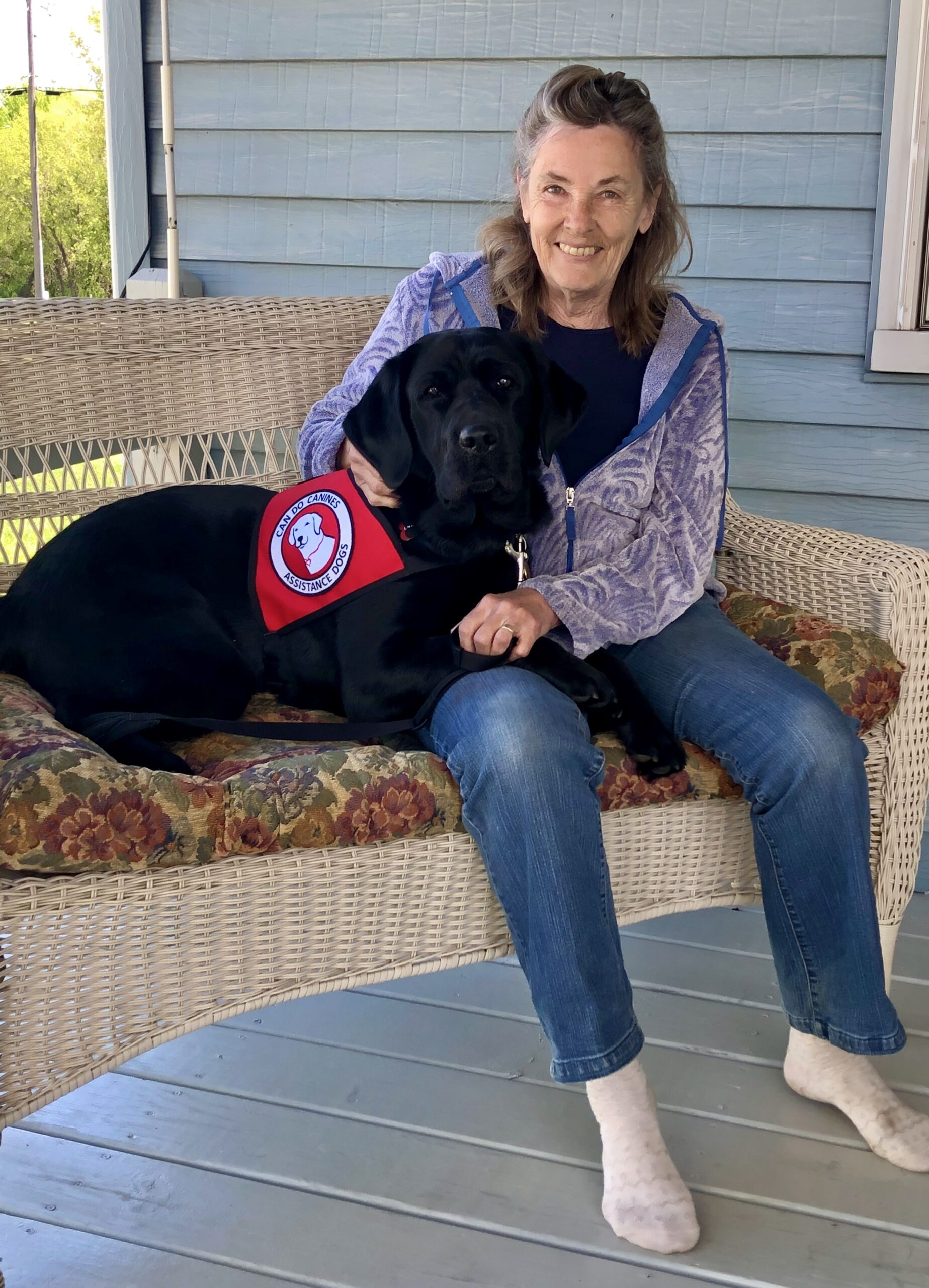 woman sitting on front step with black service dog lying across her lap